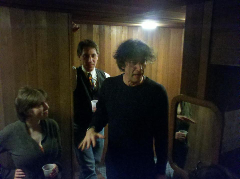 Neil Gaiman (right) shows guests the hidden sauna in the basement of the stately home he and Amanda Palmer rent in Cambridge.