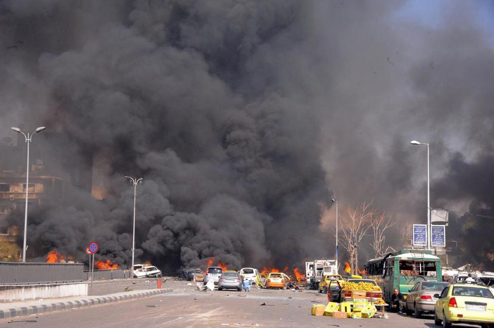 Flames and smoke rose from burned cars after an explosion shook central Damascus on Feb. 21, as seen in this photo released by the Syrian official news agency SANA.