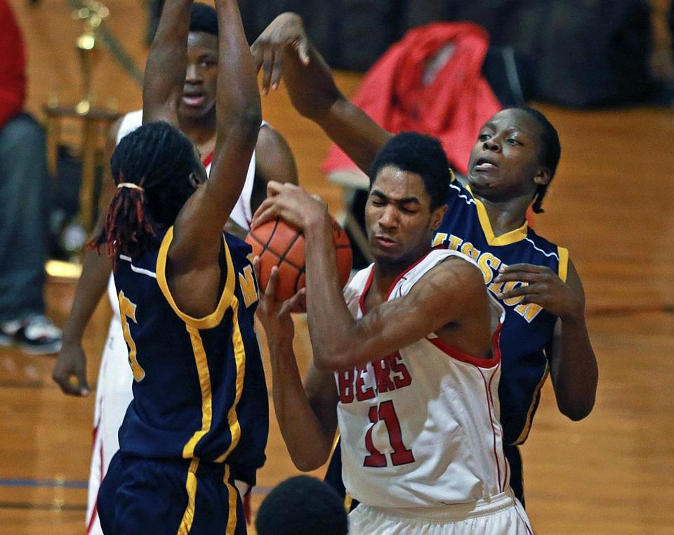 Dorchester's Dakari Wurnum (center) is surrounded by New Mission defenders Juwan Gooding (left) and Sam Freeman (right) in first half action.