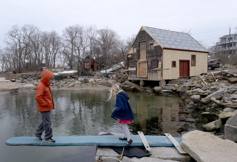 Daniel Hafey (age 8, left) and his sister Anna Hafey (6) explore Lane's Cove in the Lanesville section of Gloucester, Mass. Feb. 23, 2013, where the old fish shack (shown) is being restored. They stopped by to visit their father, one of the volunteers working.