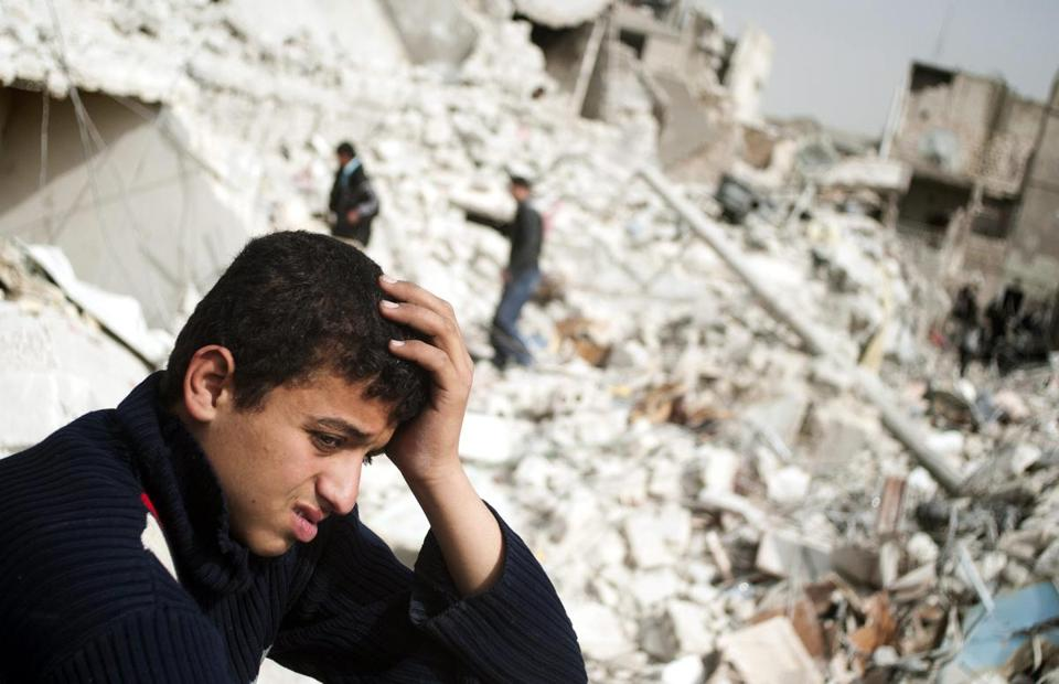 A Syrian teen watched Sunday as Aleppo residents walked through the rubble left by a recent missile attack.