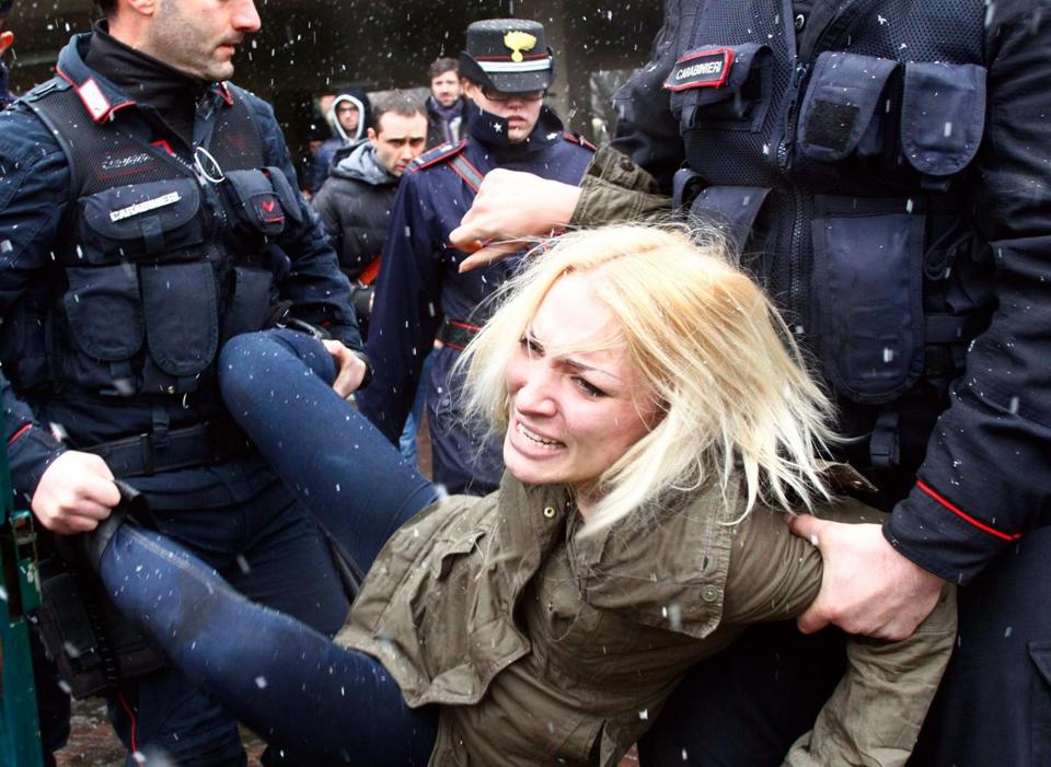 Police carried away a protester where former Italian premier Silvio Berlusconi was voting in Milan on Sunday.