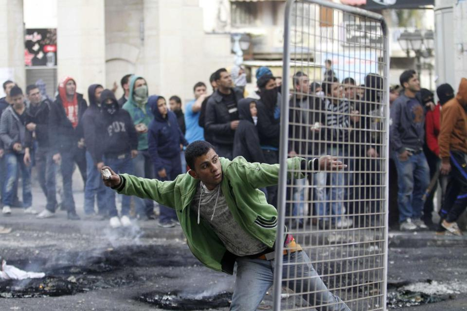 A Palestinian man threw a stone toward Israeli soldiers after the funeral of Arafat Jaradat in the West Bank on Monday.