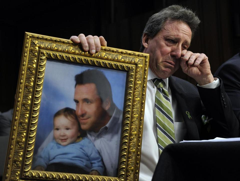 Neil Heslin, the father of a 6-year-old boy who died in the Sandy Hook massacre, holds a photo during his testimony Wednesday before the Senate Judiciary Committee.