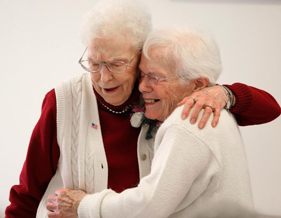 Lois Reed (left) hugs her neighbor Barbara Sleezer.