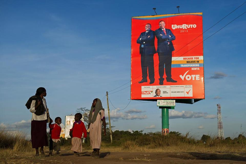 A family walked past a campaign billboard for presidential candidate Uhuru Kenyatta and his running mate, William Ruto, on the outskirts of Nairobi on Feb. 26.