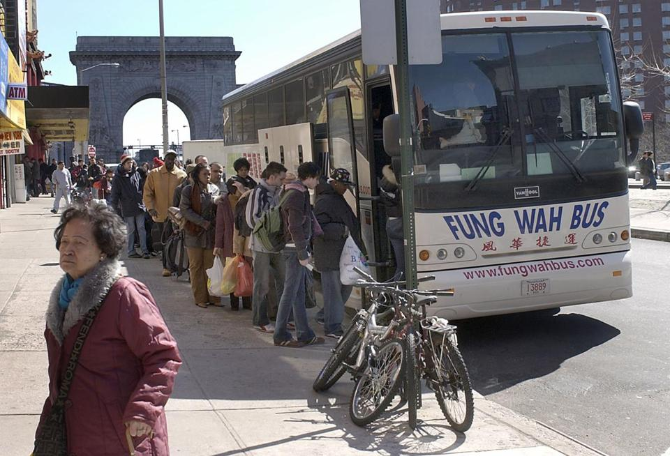Passengers line up in Chinatown in New York City to board a Fung Wah bus to Boston.