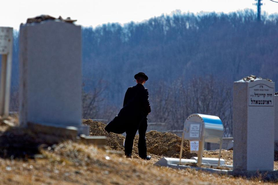 A mourner walked toward the graves of Nachman and Raizy Glauber
