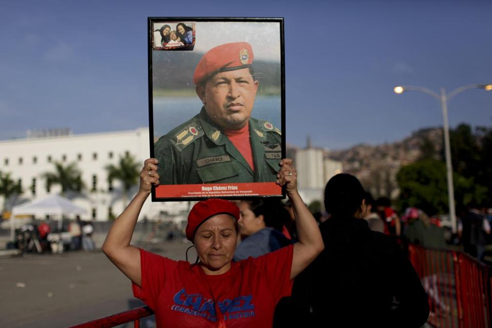 A woman holds a photo of Hugo Chavez as she waits in line to see his body in Caracas on Thursday.