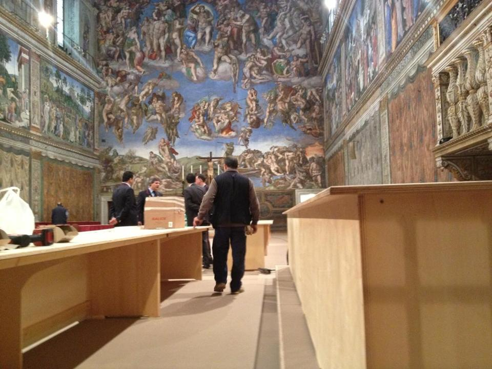 Staff worked on the long tables where the cardinals will sit during the conclave.