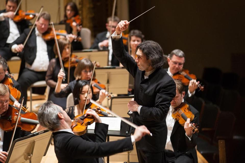Conductor Vladimir Jurowski (right) and violinist Vadim Repin (front) performing with the London Philharmonic Orchestra at Symphony Hall on Friday night.
