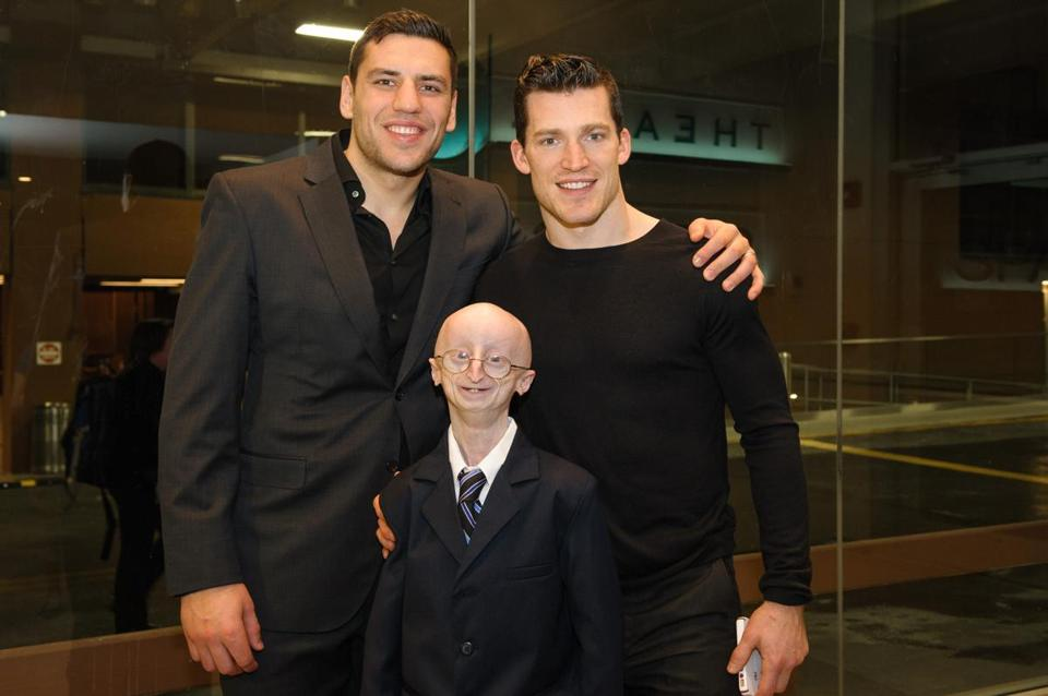 Bruins Milan Lucic (left) and Andrew Ference with Sam.
