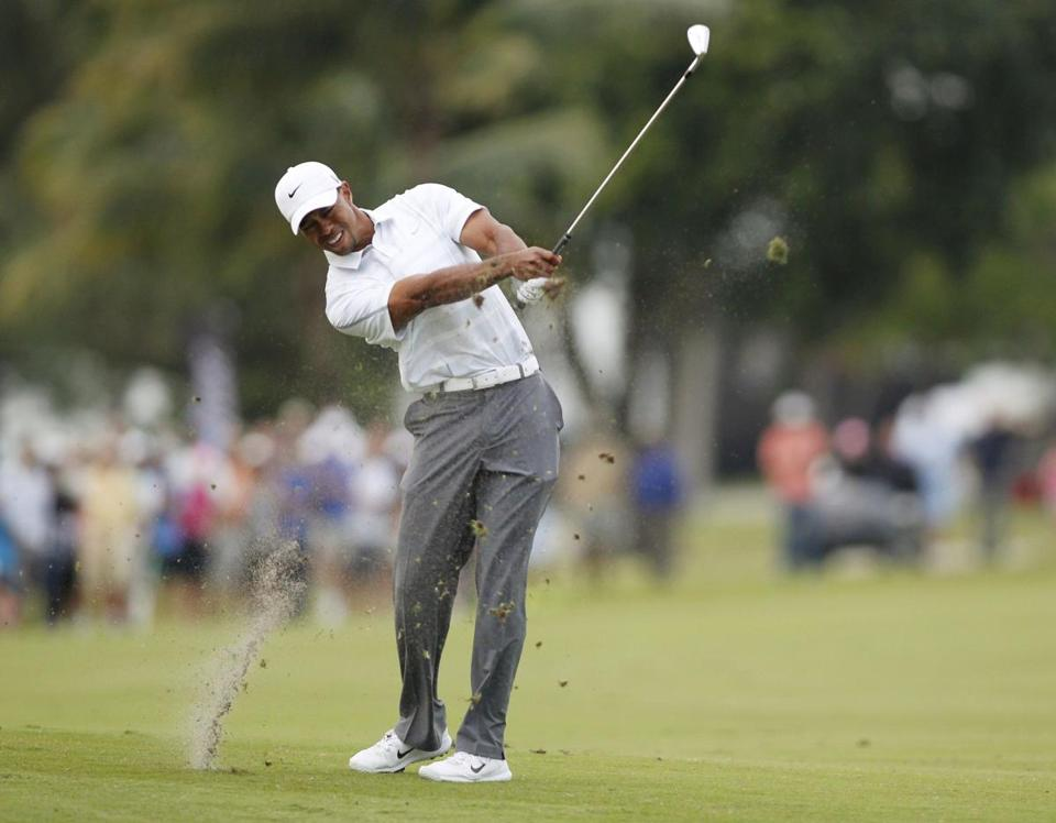 Tiger Woods hits an approach on No. 18, a shot that led to his seventh birdie of the day and a four-stroke lead.