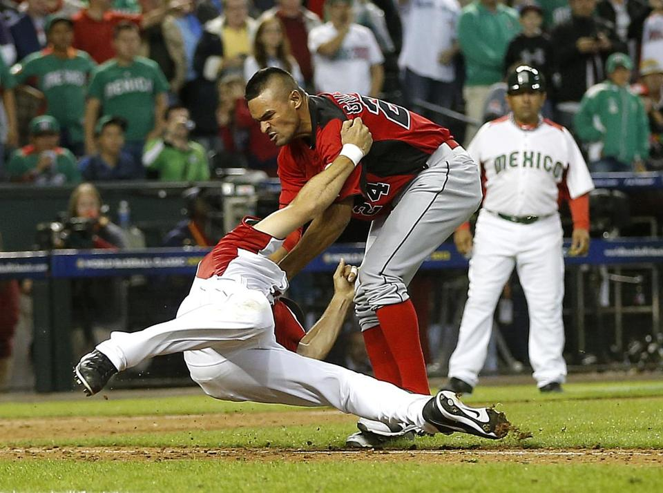 Canada's Tyson Gillies (right) tangles with Mexico's Alfredo Aceves in the midst of a wild, benches-clearing brawl during the ninth inning of a World Baseball Classic game in Phoenix. The scene was triggered by a bunt, because the WBC uses run differential as a tiebreaker.