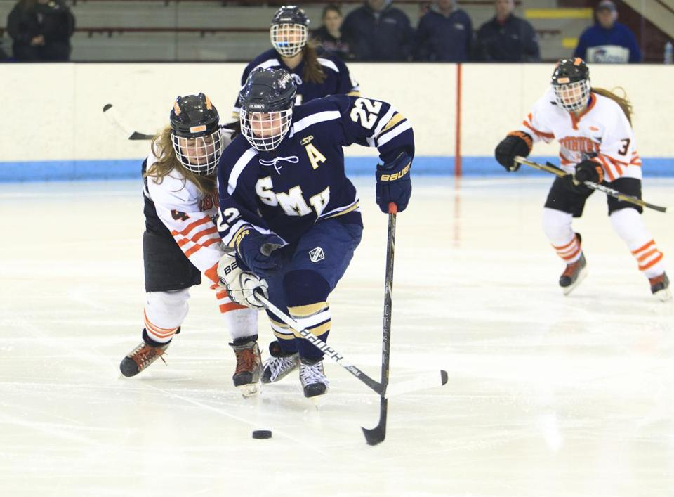 St. Mary's Kaleigh Finigan pulls away from Woburn's Ashley Moran in battle for puck.