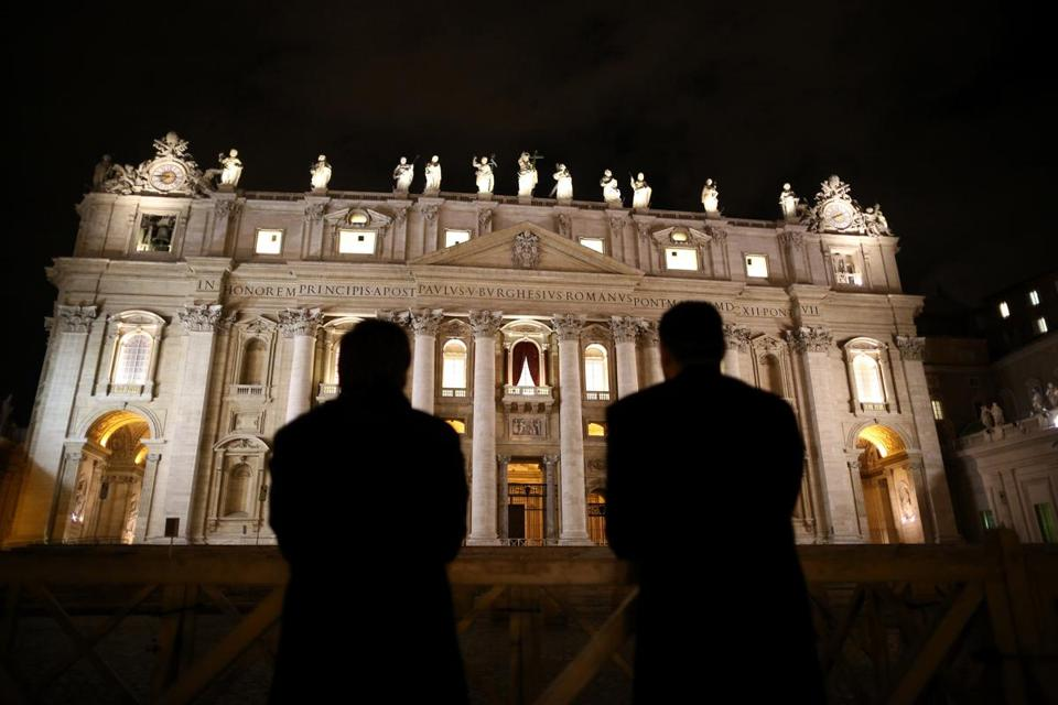 Priests looked up at a floodlit St Peter's Basilic in Vatican City on Monday.