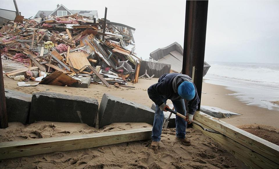 Jimmy Gravel removed posts from a house on Plum Island Tuesday. The lumber was to be used to shore up a garage.