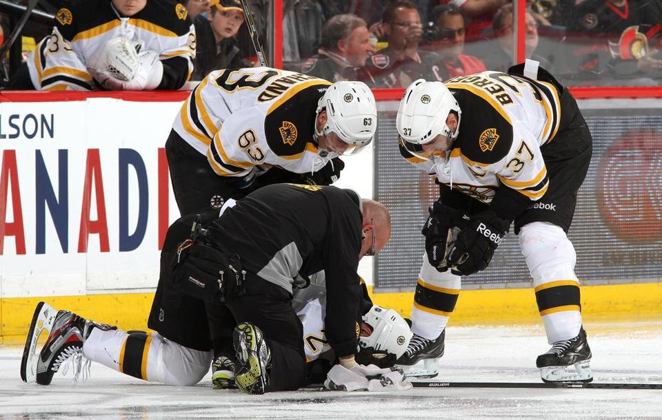A trainer tended to Chris Kelly after he was injured in the Bruins' win in Ottawa on Monday.