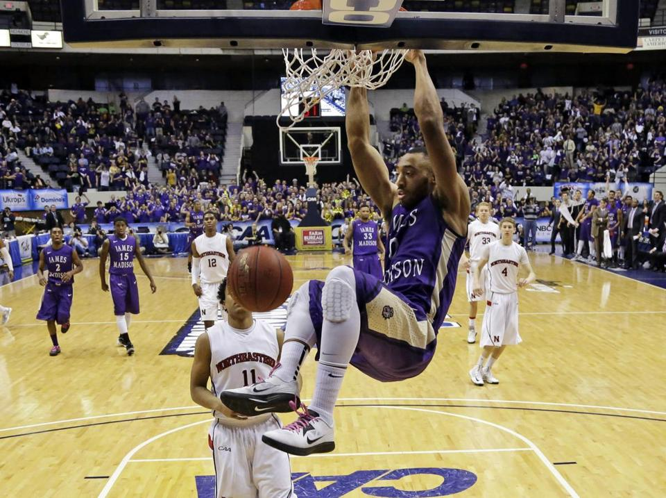 James Madison guard A.J. Davis hung on the basket after a dunk on Monday.