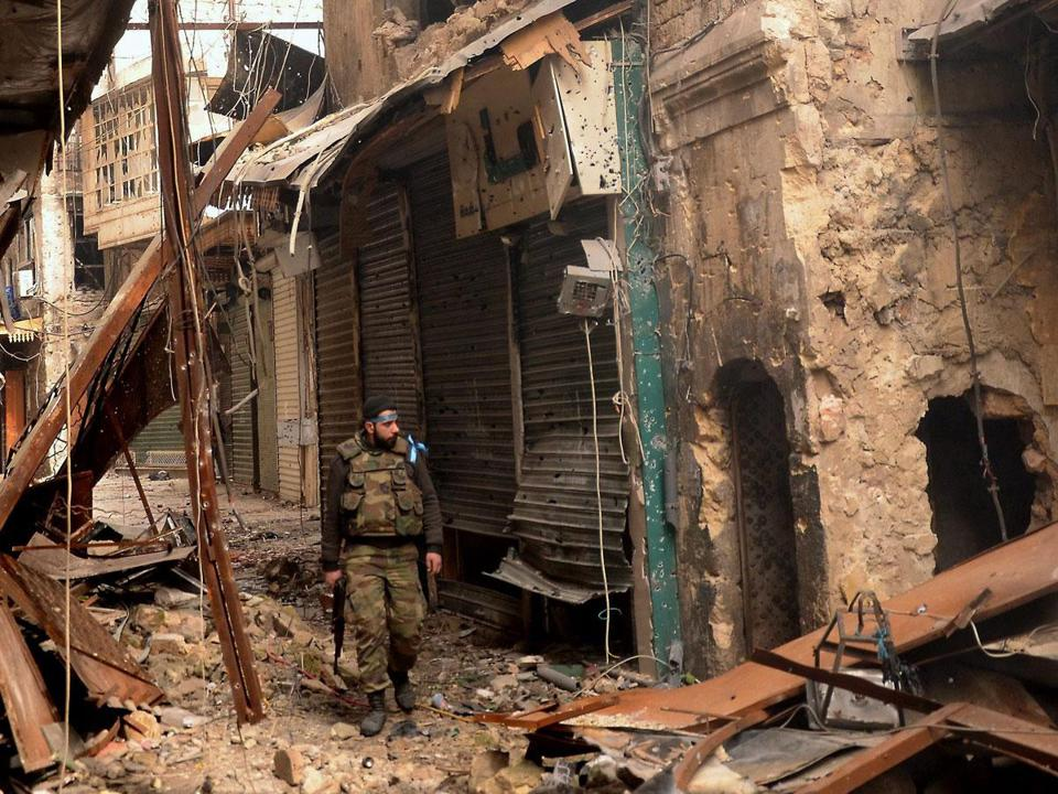 A member of the Syrian security forces inspected damage during a recent patrol in Aleppo.