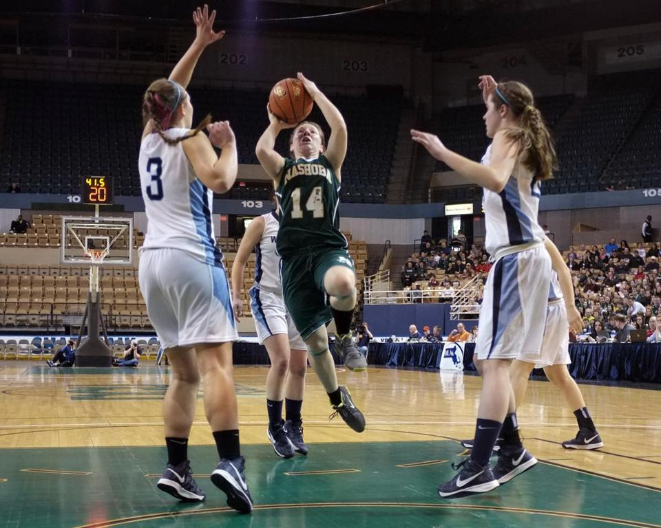 Nashoba's Cecilia Burke (14) drives through Medfield's defense during the Div. 2 Girl's State Basketball Finals at the DCU Center in Worcester.