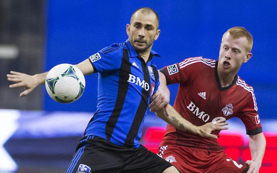 Montreal Impact's Marco Di Vaio, left, and Toronto FC's Richard Eckersley vie for possession of the ball during the second half.