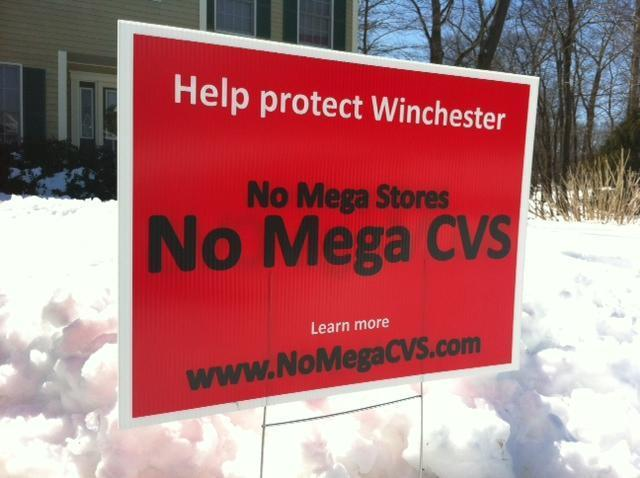 Bright red signs opposing CVS's plans for a 12,000-square-foot store have sprouted in many Winchester yards.