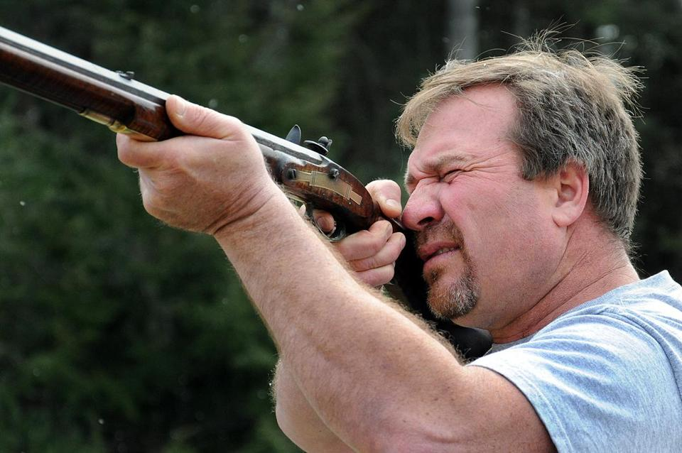 "Bill Barchant takes aim with a Kentucky Flintlock long rifle outside his Lakeville home. ""I find a safe place for unwanted guns to go,"" he says."
