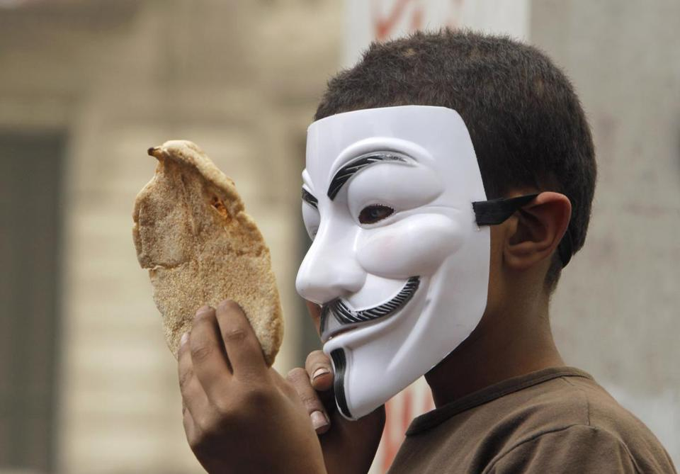 An Egyptian boy wearing a Guy Fawkes Mask held bread, a symbol of poverty, during an anti-Muslim Brotherhood demonstration in Cairo, Egypt, Friday, March 22, 2013.
