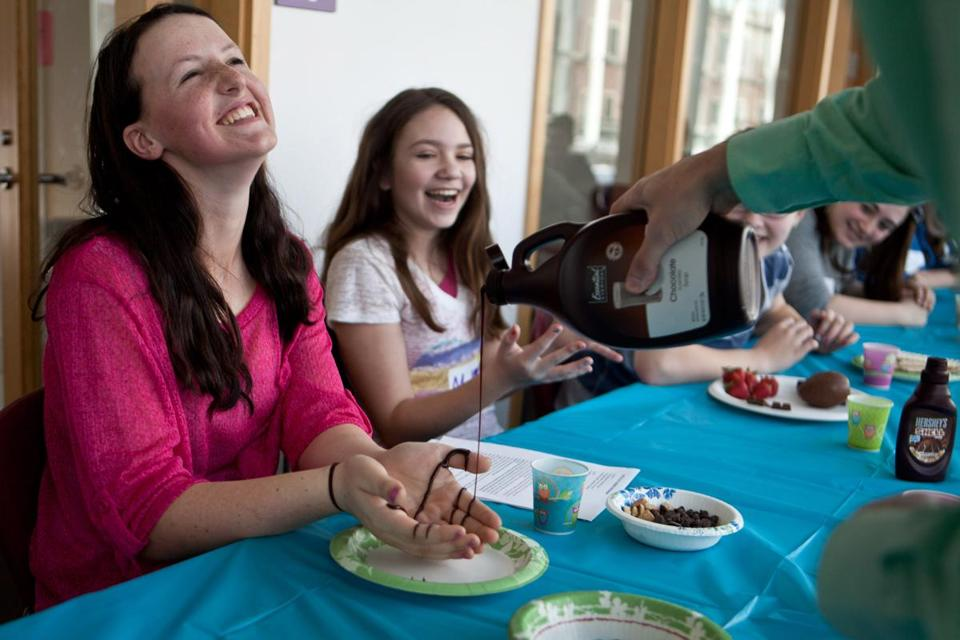 At the chocolate seder in Newton Sunday, Sophie Harlam, who helped plan the event, had her hands ritually covered in chocolate sauce. With Harlam at Hebrew College was Madi Roach.