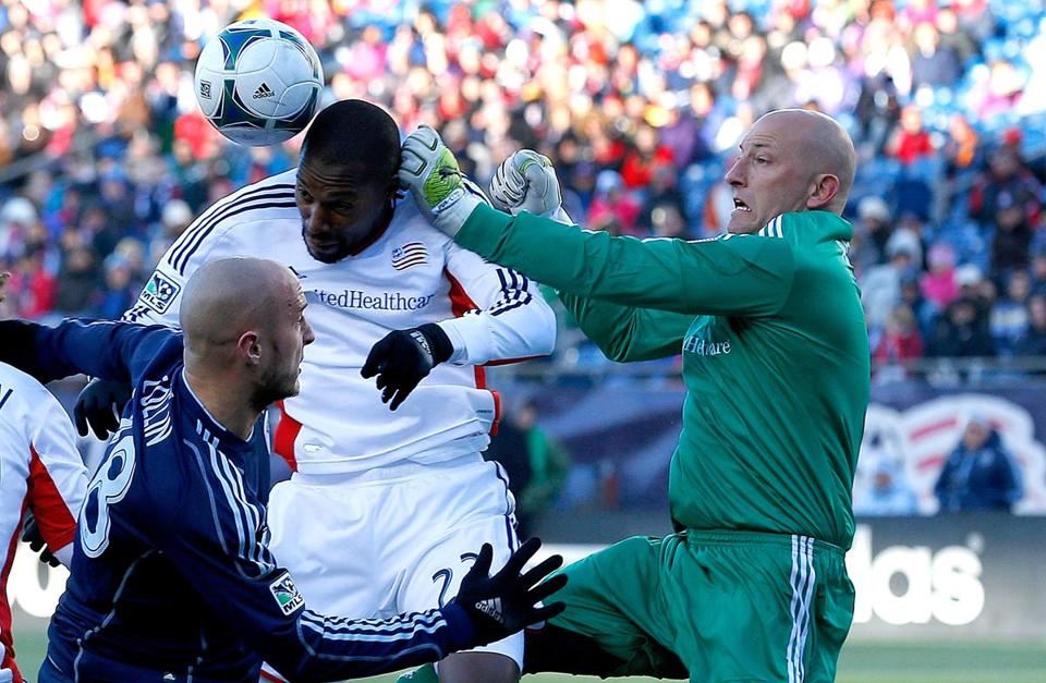 Revolution's Jose Goncalves (center) gives Matt Reis a hand in defending Aurelien Collin.