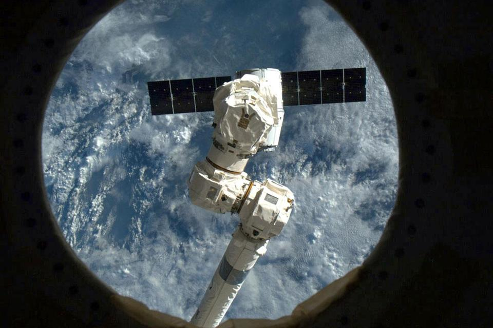 A NASA image shows the SpaceX capsule Dragon being snagged by an arm of the International Space Station this month.