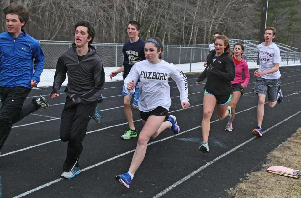 Foxborough High sophomore Liz Holmes (center) joins teammates for a training run on the Ahern Middle School track.