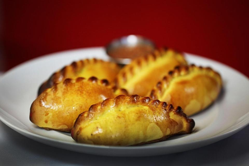 Saltenas, Bolivian pastries resembling an empanada and filled with chicken or beef, and peas, eggs, potatoes, olives, and gravy.