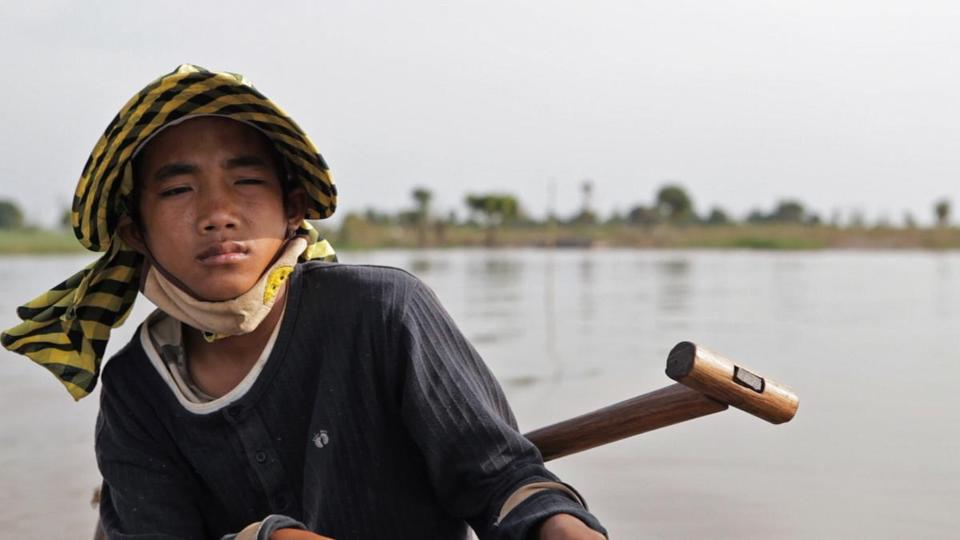 "Sari Math, a young fisherman living with his family in Cambodia, on the Tonle Sap River, in the documentary ""A River Changes Course."""