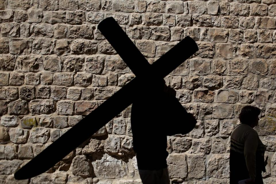 A Catholic man walked with a cross near the Church of the Holy Sepulcher in Jerusalem's Old City on Good Friday.