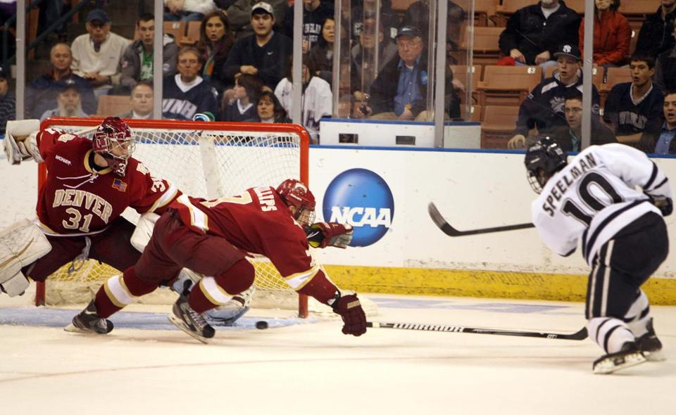Dalton Speelman, right, of UNH scored past Denver's Paul Phillips and goaltender Juho Olkinuor.