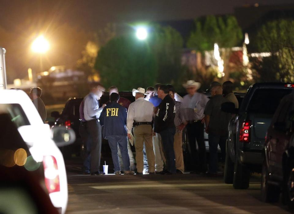 Law enforcement agents worked in Forney, Texas, where the county prosecutor and his wife were killed in their home.
