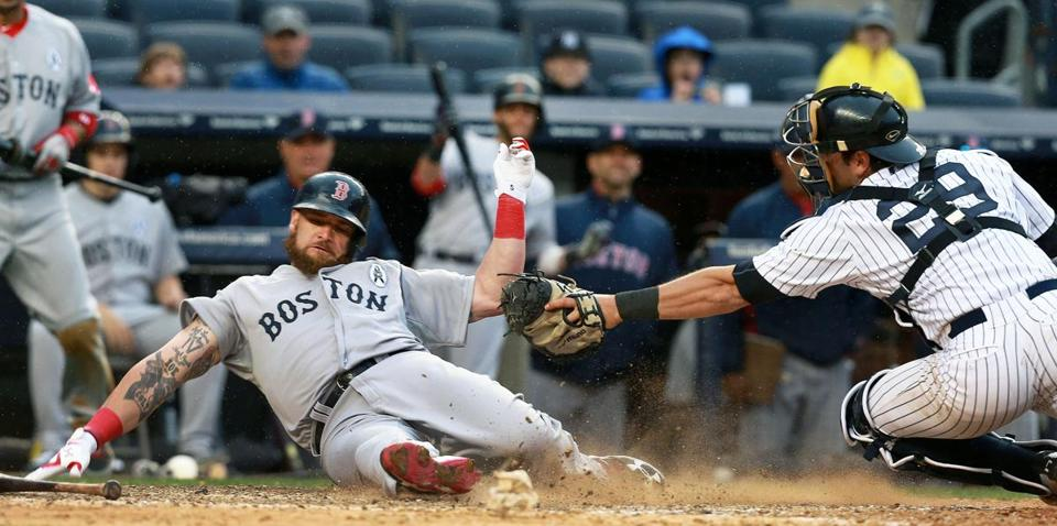 Jonny Gomes slid around the tag to score one of the Red Sox' eight runs on Opening Day.