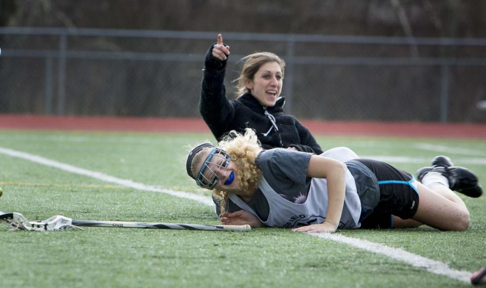 Medfield High girls' lacrosse team coach Kathleen McCullough, in back, gets taken out during practice by captain, Nicole Busa.