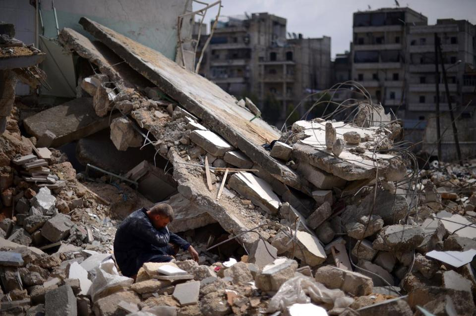 A Syrian man sat on the rubble of a building in the Al-Sukkari district of Aleppo on Friday.