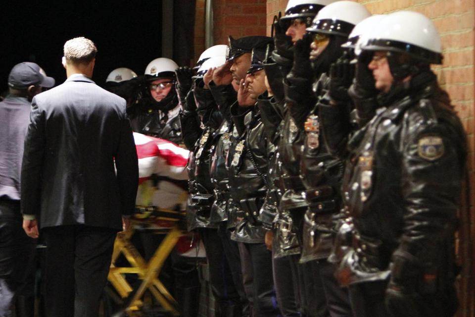 Police officers and fellow firefighters saluted Captain Michael Goodwin's body at a funeral home on Sunday.