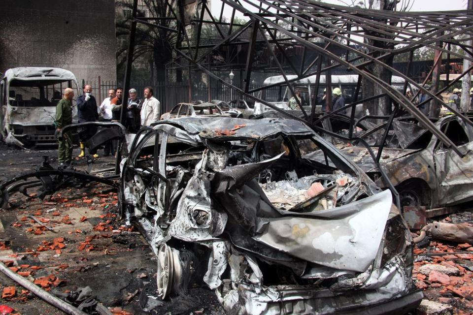 Burned cars littered the site of a car bomb explosion in Damascus Monday. Fifteen people were killed, according to the Syrian Observatory for Human Rights.