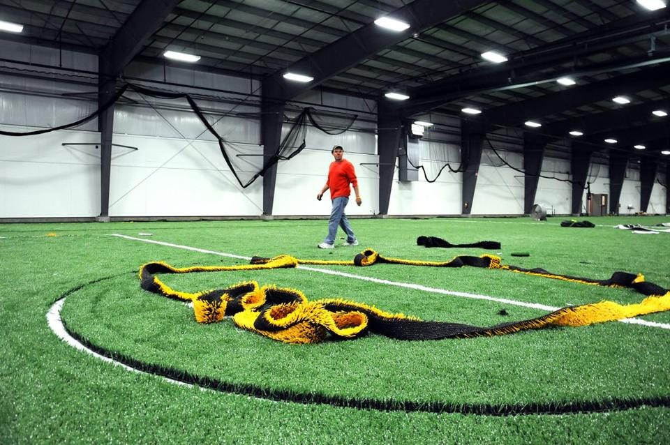 Employee Mike Lennon walks over the newly installed artificial turf  at The University Sports Complex  at Starland in Hanover.