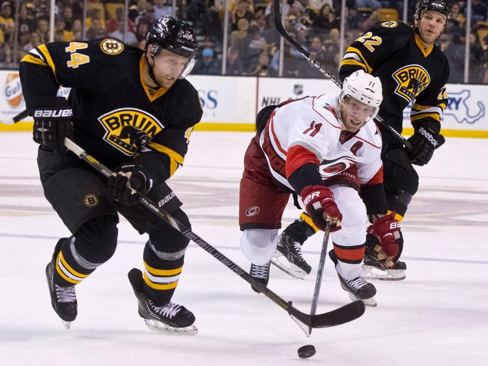 Dennis Seidenberg clears the puck away from Jordan Staal in the third period; Seidenberg had three assists.