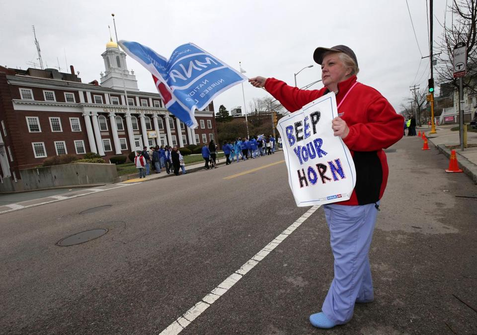 A nurse waved a sign outside Quincy Medical Center as unionized workers, nurses and supporters walked a picket line.