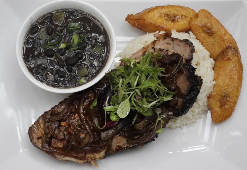 Slow-roasted pork with white rice, black beans, and plaintains.