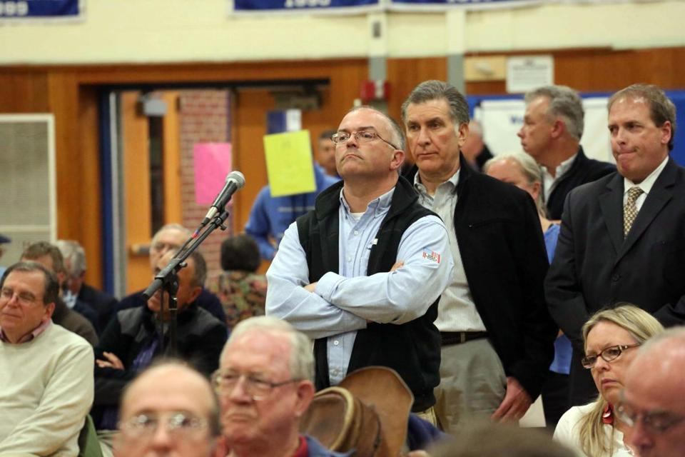 At Scituate's Annual Town Meeting, Mark McKeever (arms crossed) waits to speak about the town's wind turbine.