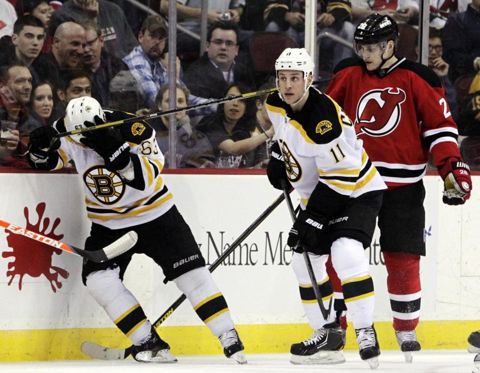 Brad Marchand held his head after being elbowed by the Devils' Anton Volchenkov. Marchand left and did not return