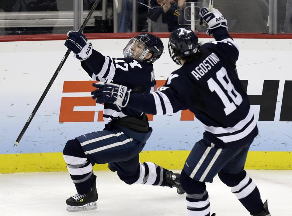 Kenny Agostino rushes to congratulate Andrew Miller for scoring in overtime and sending Yale to Saturday's championship game.